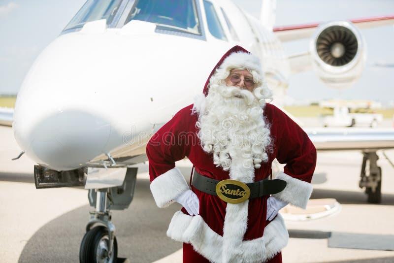 圣诞老人用在臀部的手反对私人喷气式飞机 图库摄影