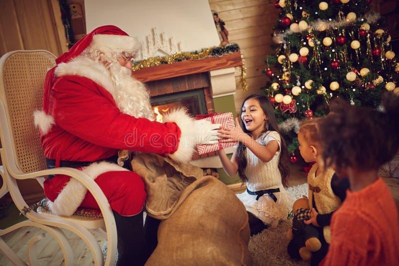 从圣诞老人的女孩快乐被采取的礼物 免版税库存照片