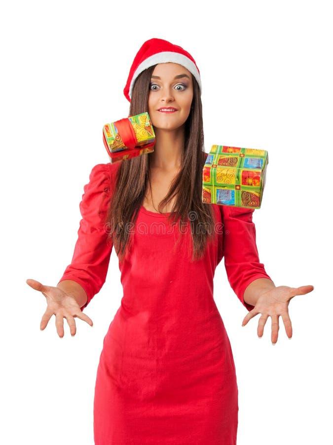 圣诞老人的帮手帽子的快乐的女孩捉住您的圣诞节礼物 免版税库存照片