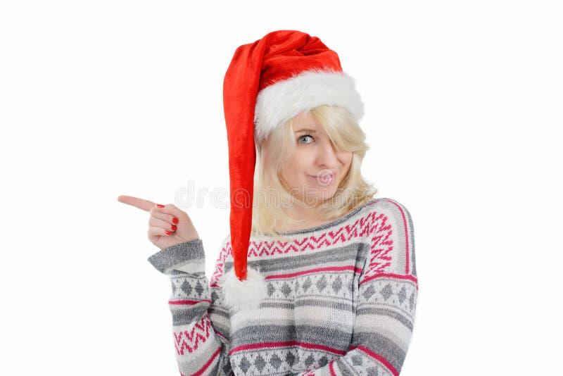 圣诞老人的帽子的一名逗人喜爱的妇女指向与手指的 库存图片
