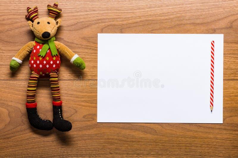 给圣诞老人的空的信件在有逗人喜爱的驯鹿玩具的一张书桌上 免版税库存图片