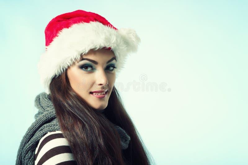 圣诞老人的红色帽子的愉快的微笑的圣诞节妇女,冬天女孩ov 免版税库存照片