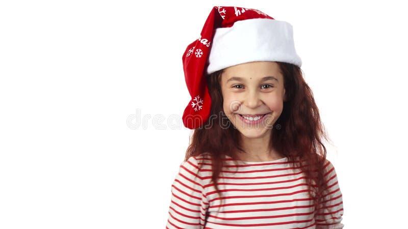 圣诞老人盖帽的一个女孩对照相机微笑 免版税库存图片