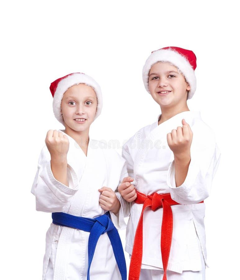 圣诞老人盖帽的两位运动员在机架站立 库存照片