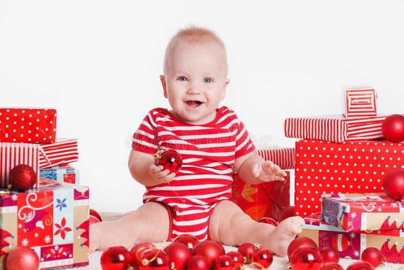 圣诞老人盖帽的可爱的孩子有堆的在的当前箱子坐地板附近。隔绝在白色背景 免版税库存图片