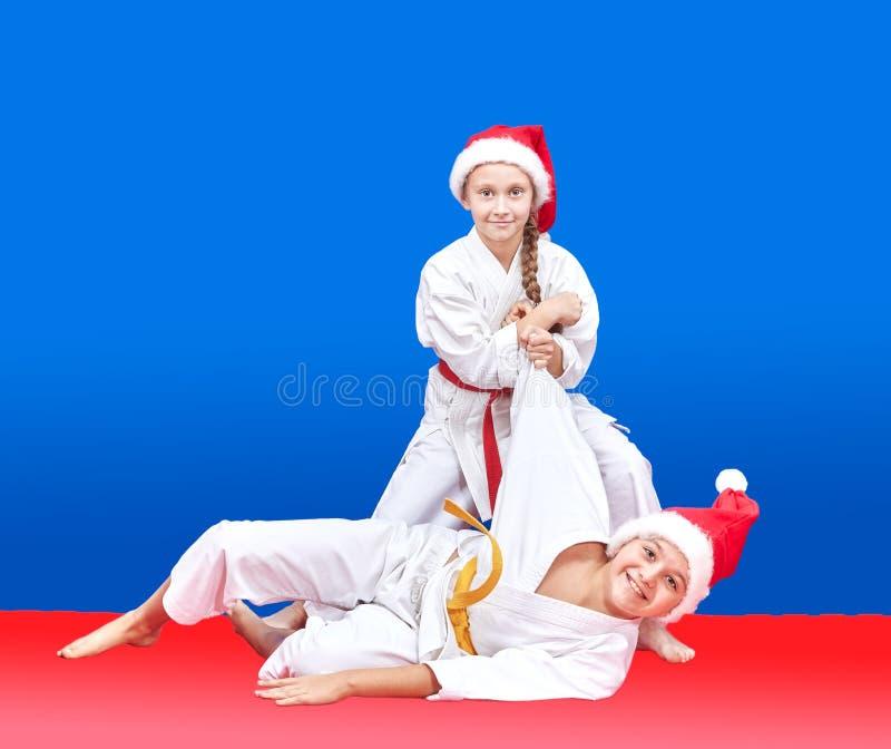 圣诞老人盖帽的孩子训练投掷 免版税库存图片