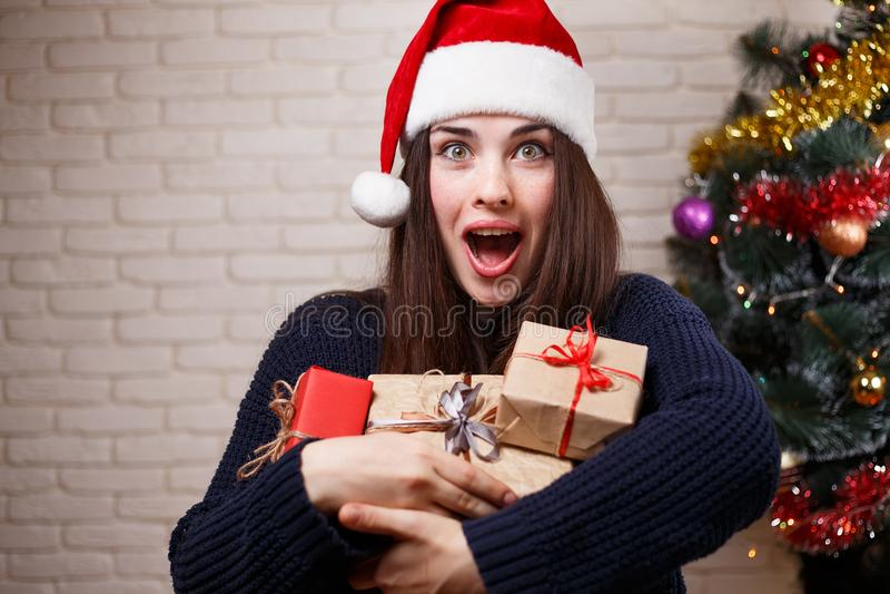 圣诞老人盖帽的年轻美丽的惊奇愉快的妇女有许多的礼物b 免版税库存图片