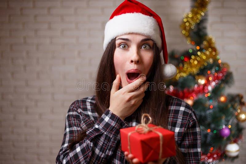 圣诞老人盖帽的年轻逗人喜爱的极端惊奇的妇女是愉快的对ge 免版税库存图片