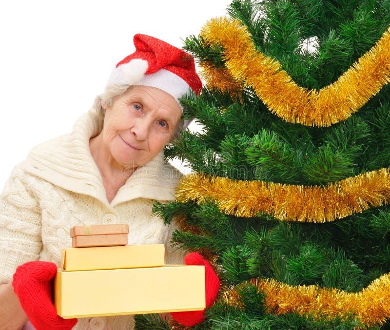 圣诞老人盖帽的祖母有圣诞节礼物的 免版税图库摄影