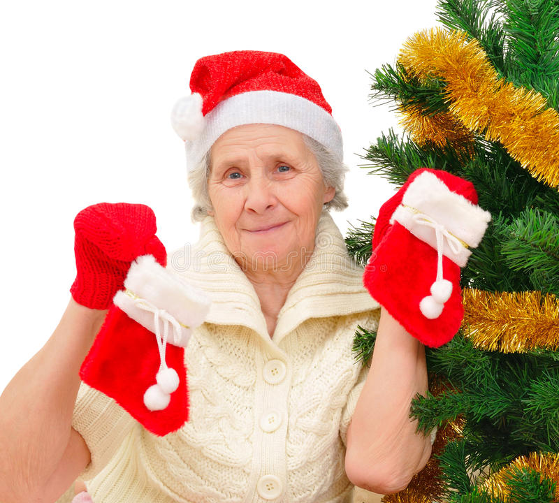 圣诞老人盖帽的装饰圣诞树的愉快的祖母画象  免版税库存图片