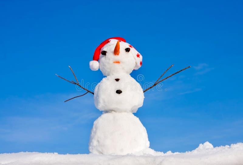 圣诞老人盖帽的雪人 免版税库存图片