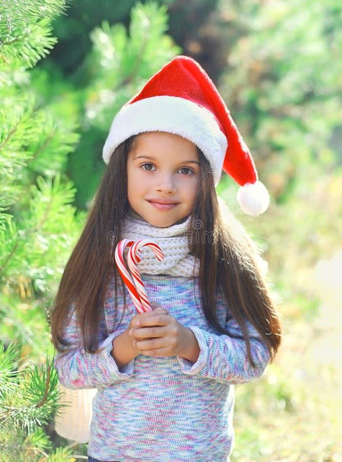 圣诞老人红色帽子的圣诞节孩子有甜棒棒糖藤茎的 库存照片