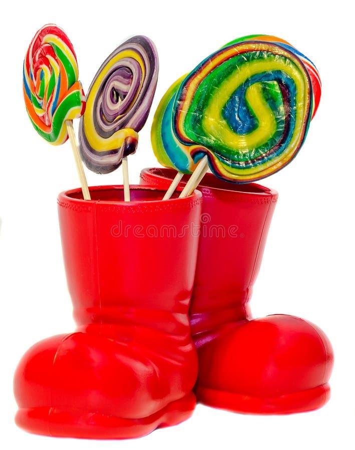 圣诞老人红色起动,有色的甜棒棒糖的, candys鞋子 与礼物礼物的圣尼古拉起动 免版税库存照片