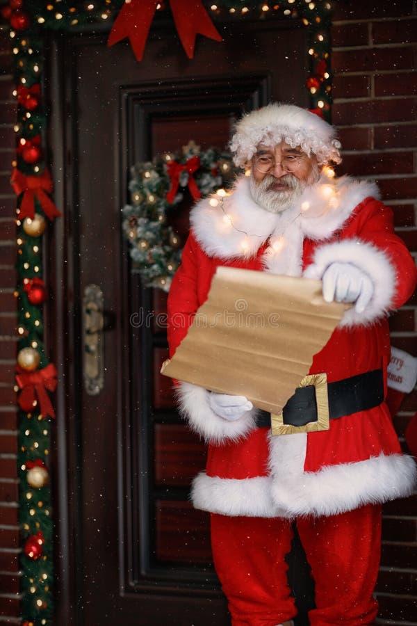 圣诞老人读了与儿童愿望的名单 免版税库存图片