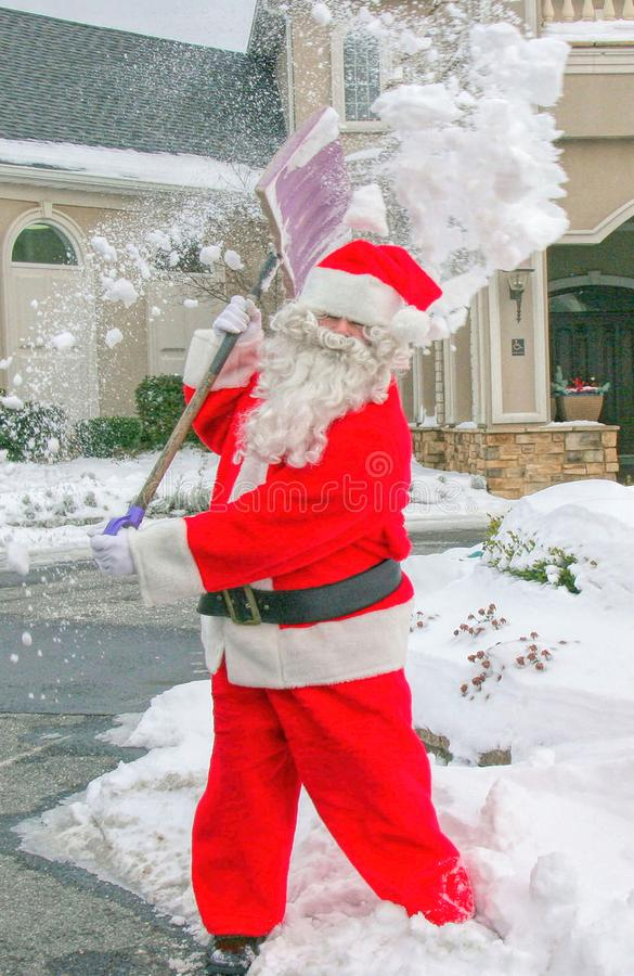 圣诞老人铲起雪 图库摄影