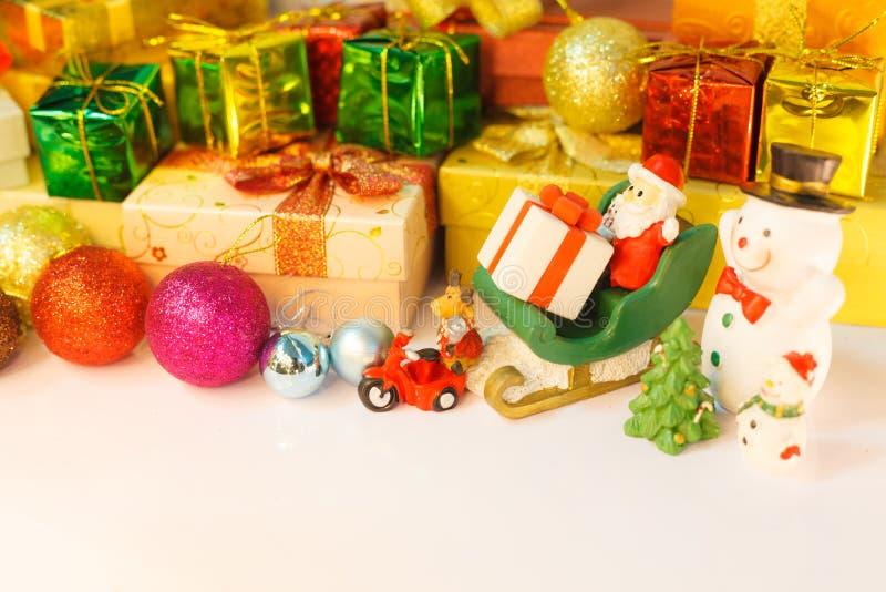 圣诞老人项目、驯鹿和雪人出发交付好孩子礼物,与装饰的圣诞礼物箱子的背景,树和 免版税库存图片