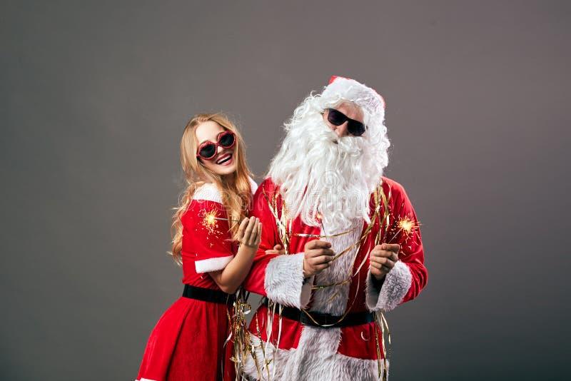 圣诞老人项目和年轻美丽的夫人 太阳镜的克劳斯在他们的手上拿着闪烁发光物在灰色背景 免版税图库摄影