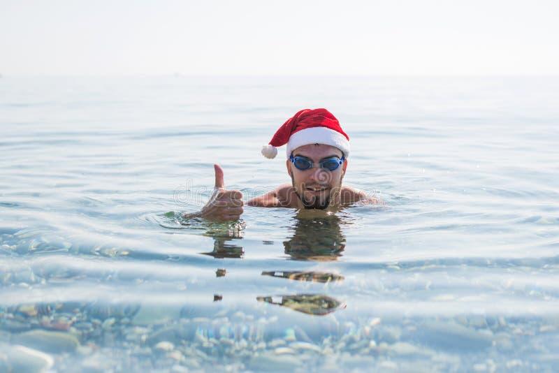 圣诞老人项目帽子和游泳的风镜赞许的,圣诞节背景人 在热带国家放松在冬天,新年 免版税图库摄影
