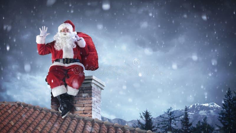 圣诞老人项目招呼在屋顶 库存图片