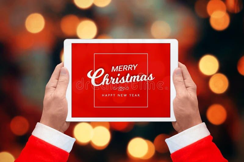 圣诞老人项目拿着在横拍的片剂与圣诞快乐和Hanppy新年问候 免版税库存图片