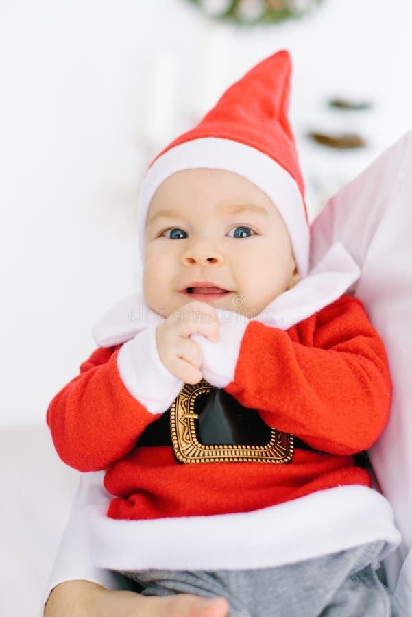 圣诞老人项目衣服的一个五个月小孩在父母的手上说谎 库存图片