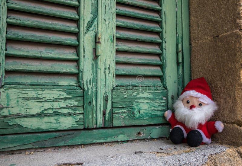 圣诞老人项目,玩偶玩具,在木快门旁边 库存图片