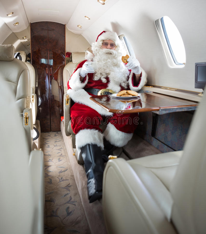 圣诞老人饮用曲奇饼和牛奶在私人喷气式飞机 免版税库存照片