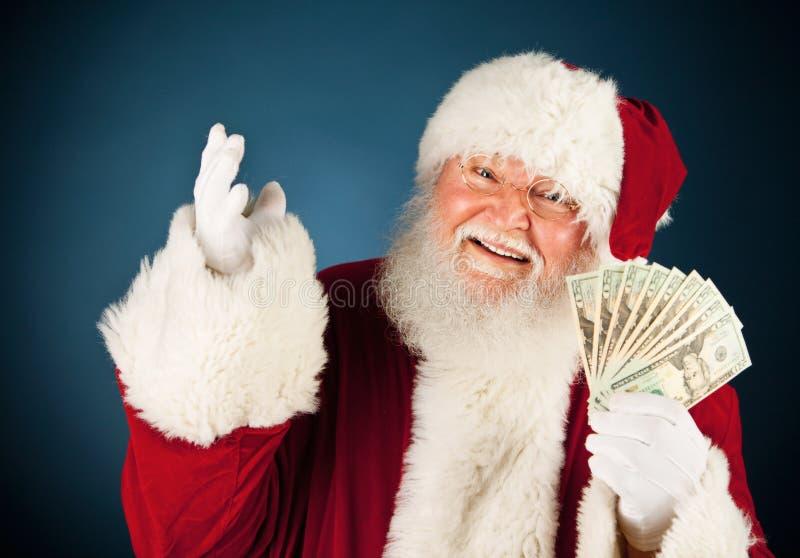 圣诞老人:圣诞老人藏品被扇动的现金 库存照片