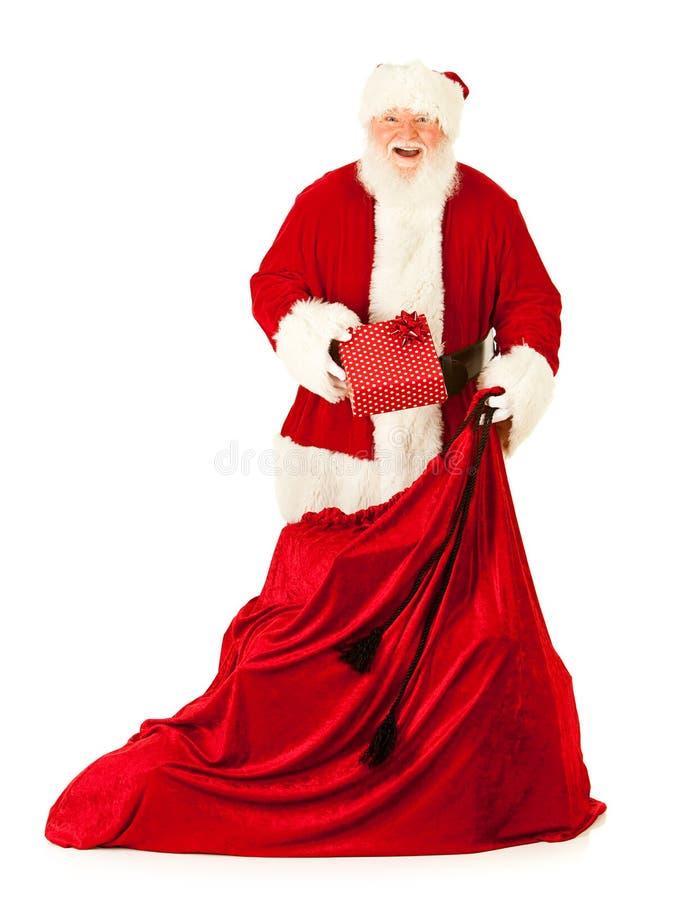 圣诞老人:拉扯从大袋的一件礼物 免版税库存图片