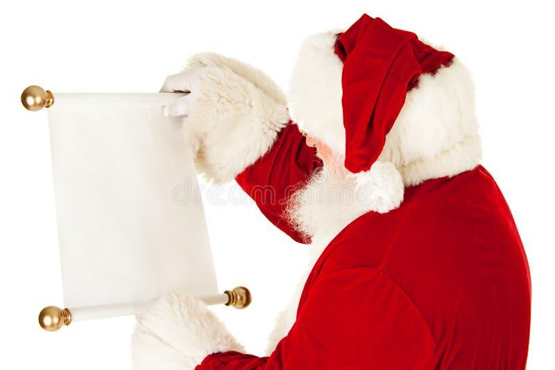 圣诞老人:拿着圣诞节名单纸卷 库存图片
