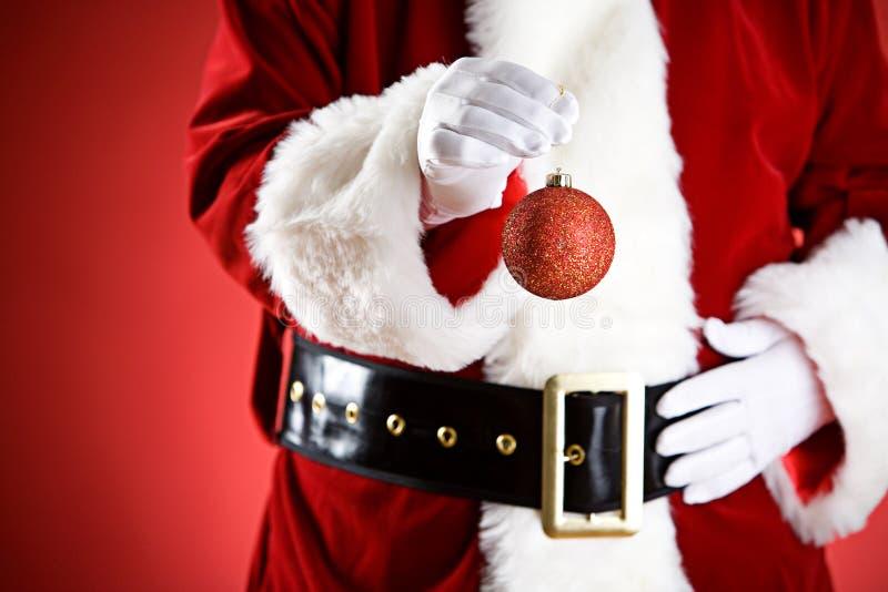 圣诞老人:拿着圣诞节装饰品 免版税库存图片