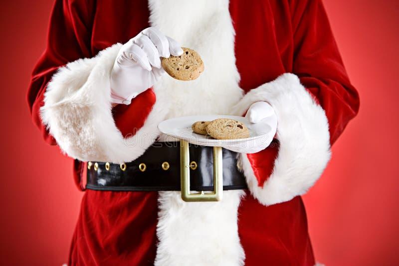 圣诞老人:拿着曲奇饼板材  免版税库存照片