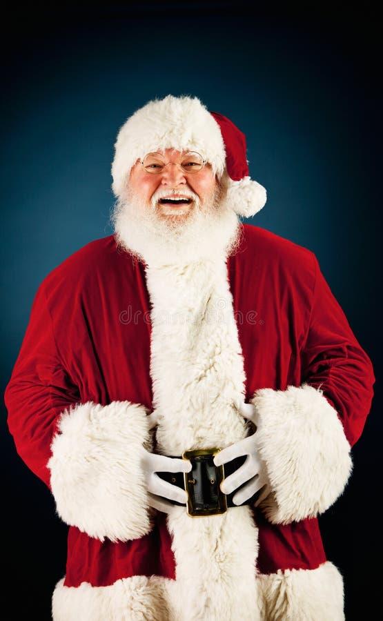 圣诞老人:笑和握腹部 库存图片