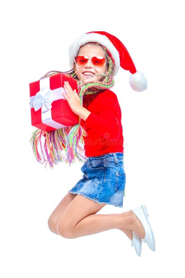 圣诞老人` s帽子的女孩 拿着箱子圣诞节礼物的小逗人喜爱的女孩画象,小女孩拥抱她的礼物以愉快 库存图片