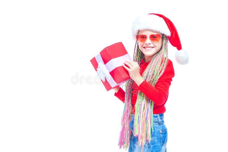 圣诞老人` s帽子的女孩 拿着箱子圣诞节礼物的小逗人喜爱的女孩画象,小女孩拥抱她的礼物以愉快 免版税库存图片