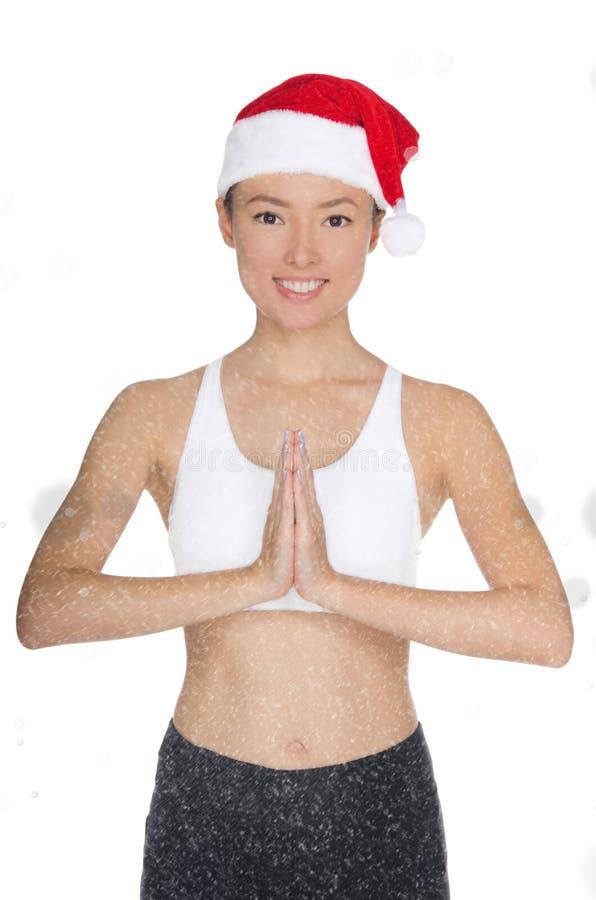 圣诞老人` s帽子的微笑的亚裔妇女参与健身 免版税库存图片