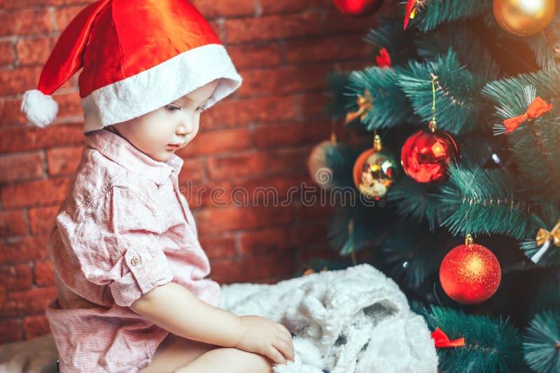 圣诞老人` s帽子的愉快的矮小的婴孩在圣诞树附近坐假日夜 新年` s假日和圣诞树 免版税库存照片