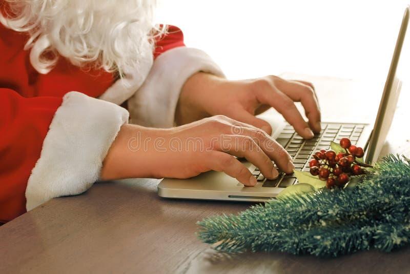 圣诞老人s手和计算机 免版税库存照片