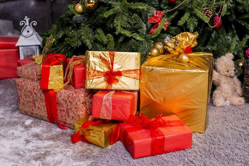 圣诞节、假日、礼物、新年和庆祝概念 礼物盒和玩具熊在x-mas树下在地板上 图库摄影