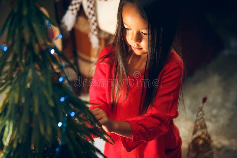 圣诞节、假日和童年概念-红色衣裳的愉快的女孩装饰自然杉树的 图库摄影