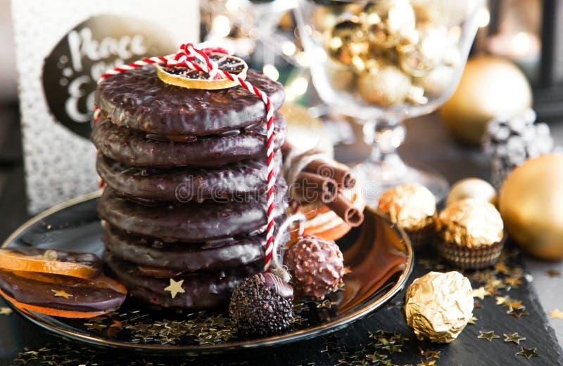 圣诞节、xmas姜面包与杯香槟和甜点,曲奇饼在黑色的盘子,金黄球和五彩纸屑用桂香, 免版税库存照片