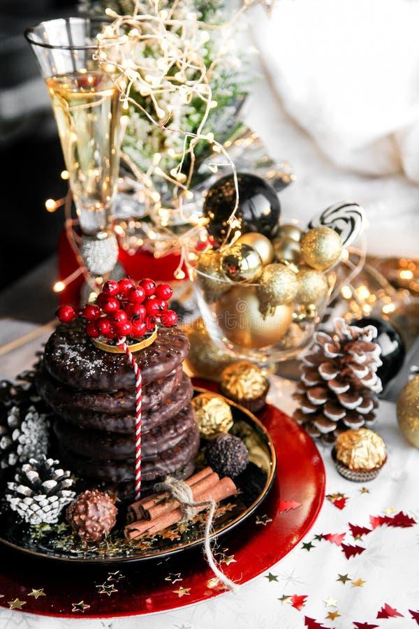 圣诞节、xmas姜面包与杯香槟,花揪、山脉灰和甜点,曲奇饼在红色板材,金黄球和 免版税库存照片