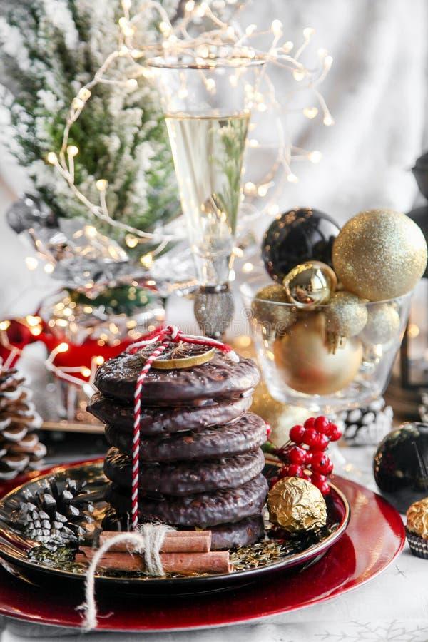 圣诞节、xmas姜面包与杯香槟,花揪、山脉灰和甜点,曲奇饼在红色板材,金黄球和 库存图片