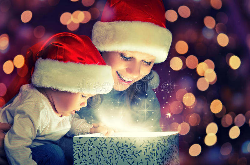 圣诞节不可思议的礼物盒和一个愉快的家庭母亲和婴孩 库存照片
