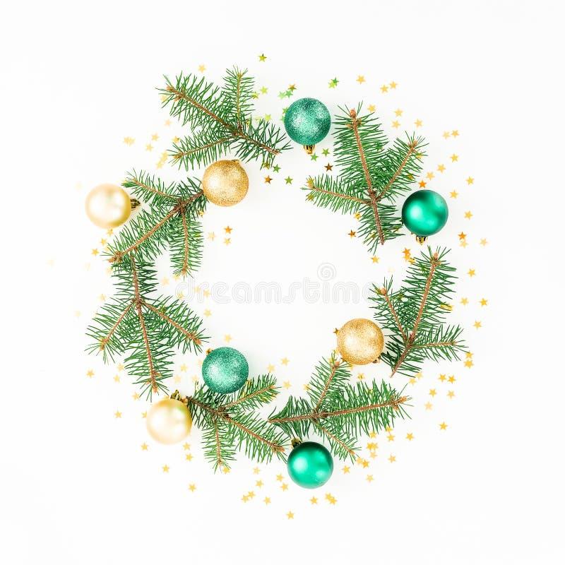 圣诞节与冬天分支、金黄球和五彩纸屑的花圈框架在白色背景 平的位置,顶视图 免版税库存图片