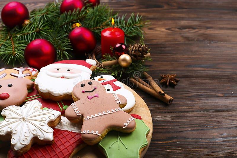 圣诞节与杉树的姜饼曲奇饼的各种各样的类型分支,肉桂条、茴香星,蜡烛和装饰接近  库存照片