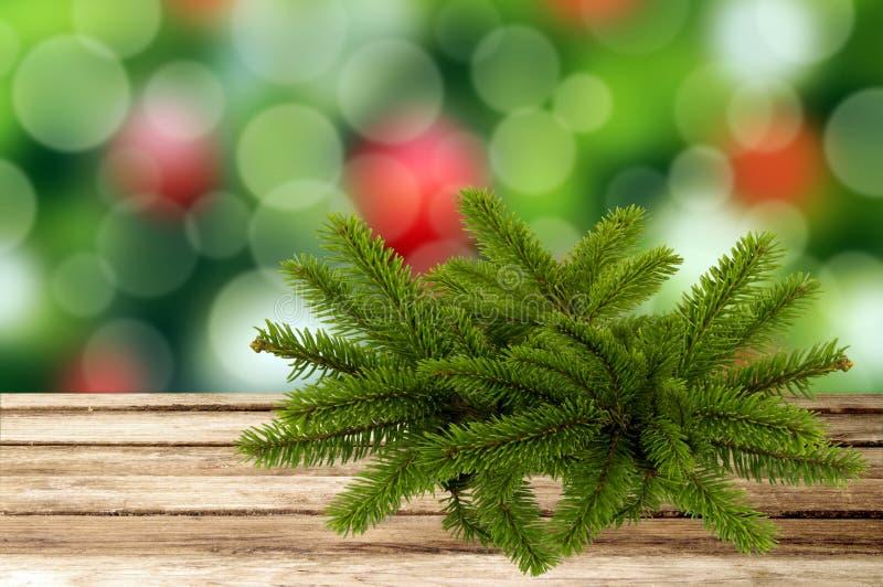 圣诞节与树枝的假日背景在木桌ov上 免版税库存图片