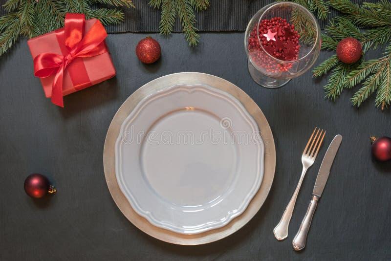 圣诞节与红色装饰和礼物的桌设置在黑色 顶视图 Xmas党 免版税库存照片
