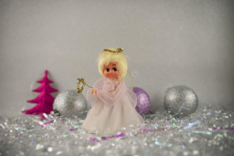 圣诞节与老葡萄酒手工制造神仙的树轻便短大衣和闪烁树装饰中看不中用的物品的摄影图片在背景中 免版税库存图片