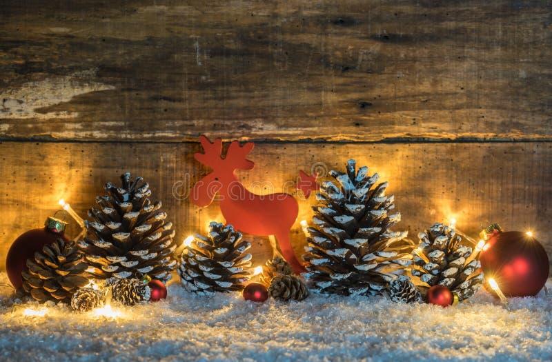 圣诞节与自然杉木锥体、球、驯鹿和光的背景装饰在雪 免版税库存照片